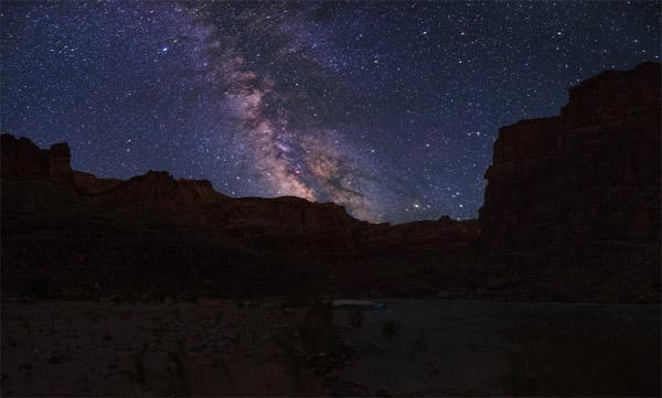 در اعماق Grand Canyon،رودخانهی کلرادو توسط شب به آغوشکشیدهشدهاست.راه شیری تابستانی در آسمان تاریک این سایت میراث جهانی واقع در آریزونای شمالی در حال درخشیدن است.
